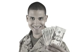 A soldier holding up a hundred dollars in twenties