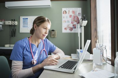 Nurse writing a resignation letter using a laptop computer.
