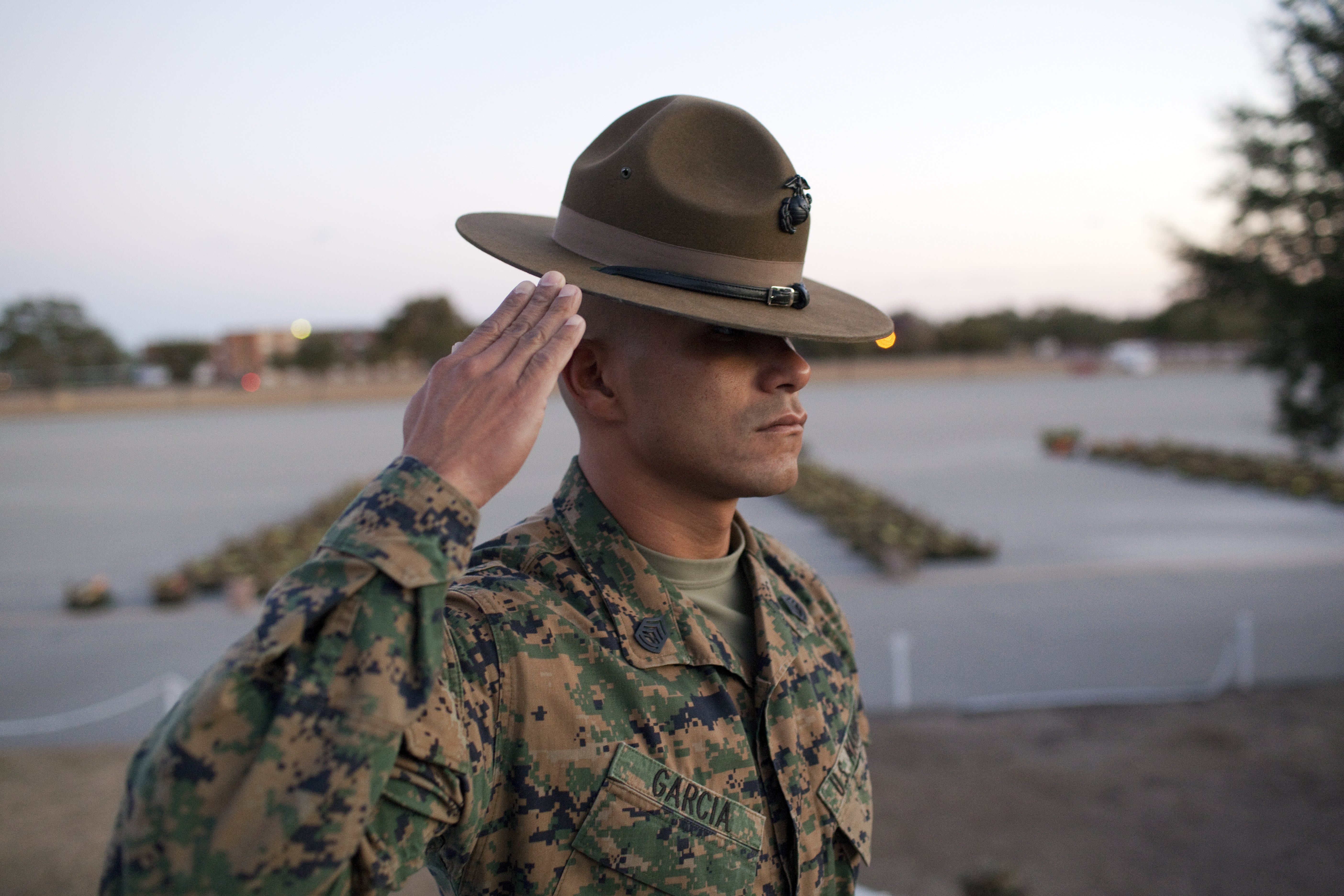 A US Marine Corps Drill Instructor salutes during a dawn ceremony
