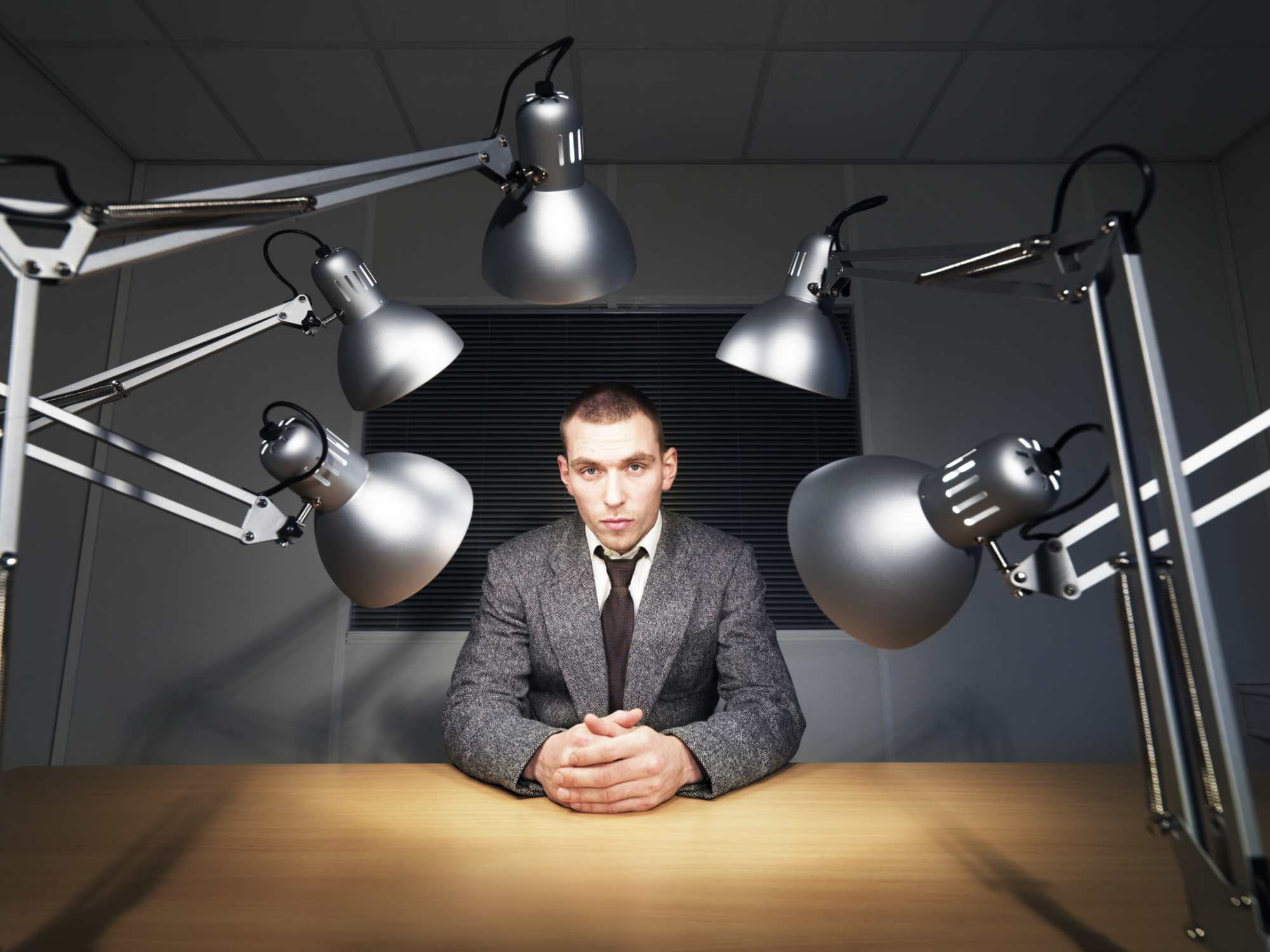 A man sitting at a desk with lights pointed at him.