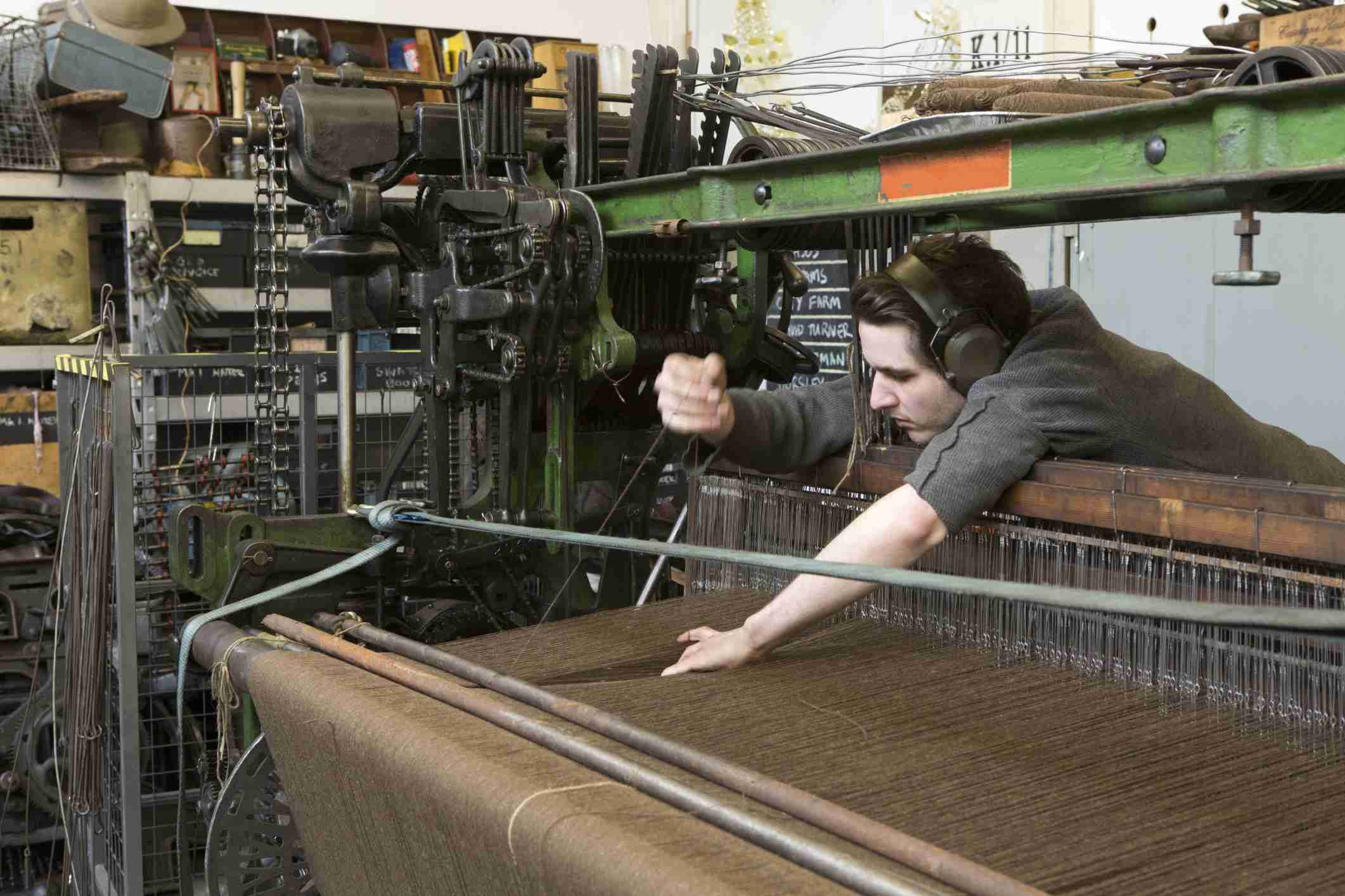 Man working in Textile Manufacturing at a large loom