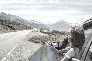 Vacationing woman parked on roadside looking at map with mountains in the background