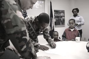 Erick Davis participates in a National Guard enlistment ceremony with his family at a recruiting center in Alexandria, Virginia.