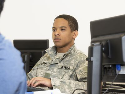 a military service member in a classroom working on a computer