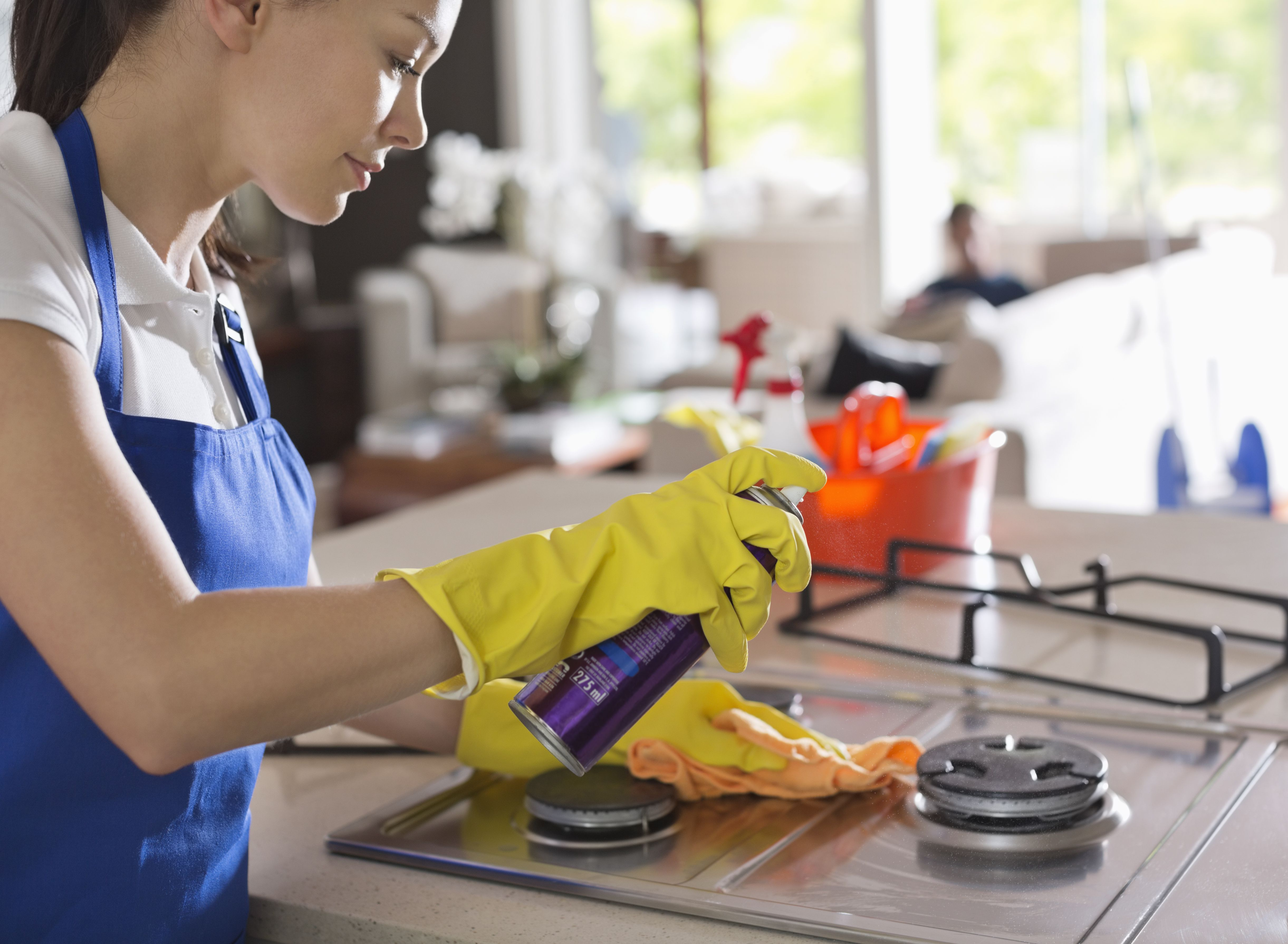Female maid wearing gloves cleaning a stove top