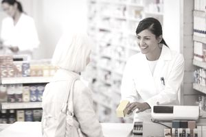 Pharmacy technician handing medication to customer in drug store
