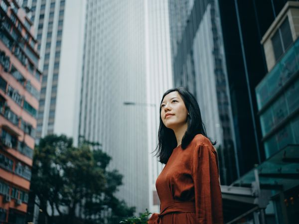 Low angle portrait of confidence young woman standing against highrise city buildings in city