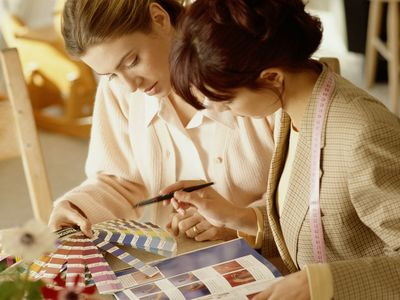 TWO WOMEN AT HOME WORKING ON INTERIOR DECORATIONS