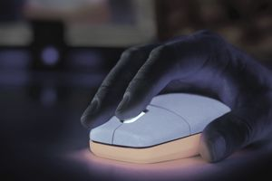 A photo of a hand on a glowing computer mouse.