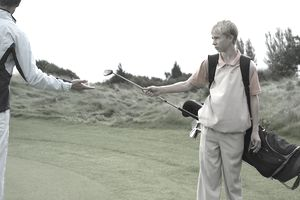 male teenage caddy giving golf club to man