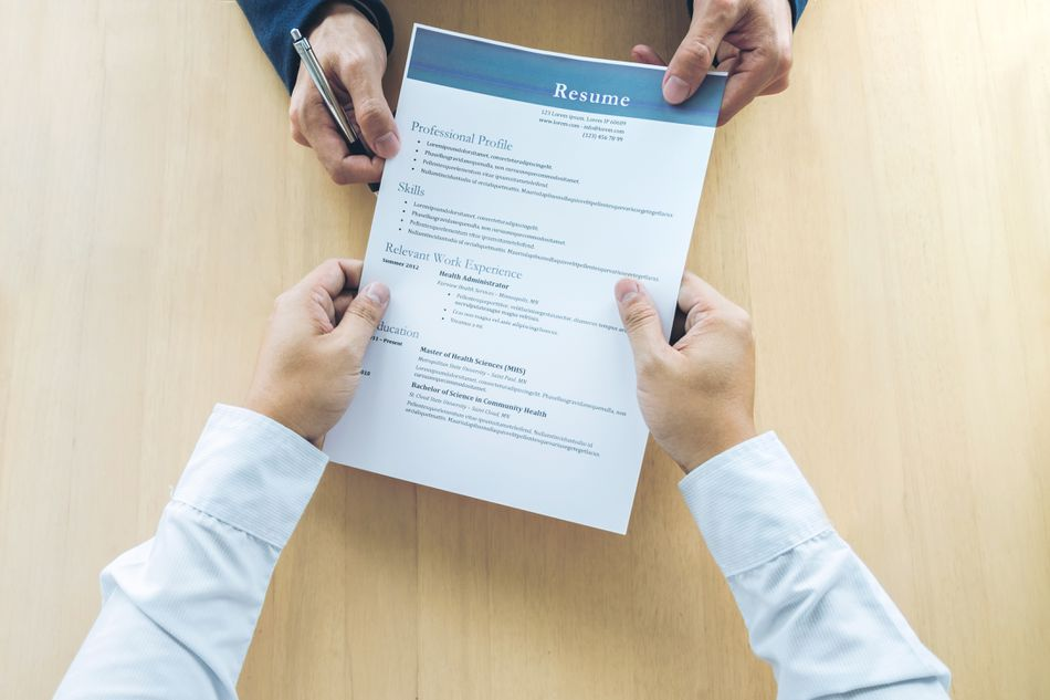 Cropped Hands Of Business People Holding Resume On Table In Office