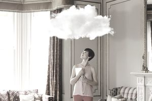 Woman in living room looking at cloud above head