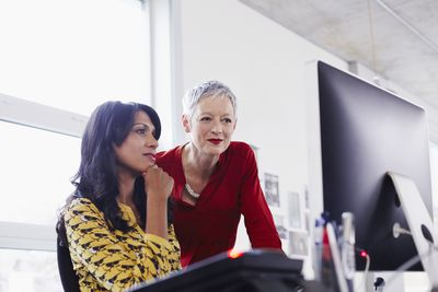 Mature business woman listens to her younger boss as they review a report.