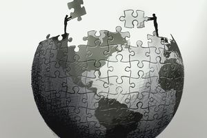 Businessmen working together on large jigsaw puzzle of globe