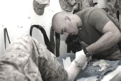 Navy Corpsmen providing care for fellow soldier