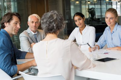 Woman using a well-organized agenda to run a successful meeting in an office.