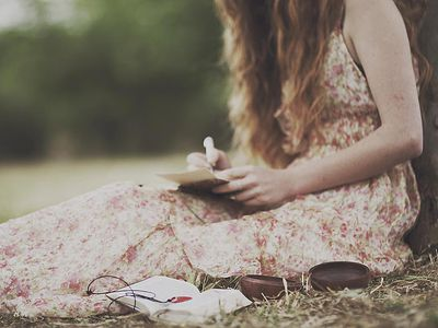 A woman sitting against a tree writing a letter
