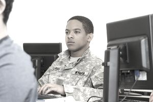Black soldier using computer in class