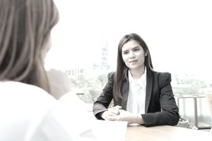Businesswoman Taking Interview Of Woman Sitting On Desk Against Clear Sky