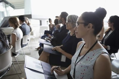 Attentive businesswoman listening in conference audience