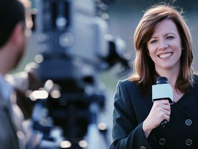 Television newswoman reporting on location (focus on woman)