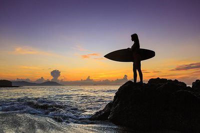 Young woman with surfboard on beach