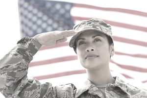 soldier saluting with the American flag in the background