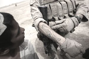 A soldier displaying a tattoo on his forearm to a young Arab boy.