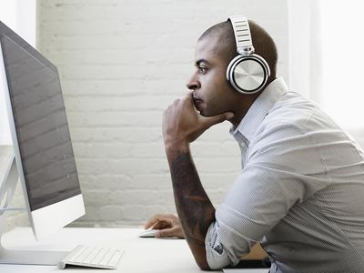 Male music agent sitting on computer with headphones reviewing concert he booked