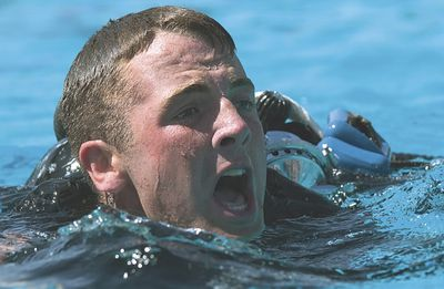 Navy sailor struggles during water physical testing.
