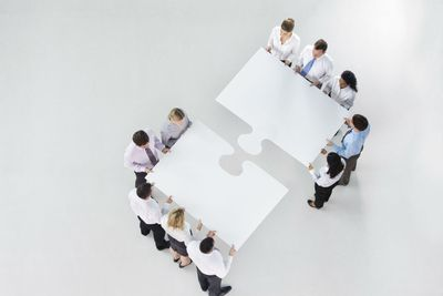 Two groups of business professionals holding pieces of jigsaw puzzles as they move to put them together