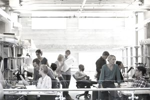 An open office with casual dressed workers interacting shows an open company culture.
