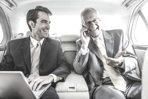 Businessmen working in backseat of car