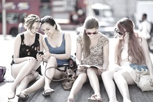 Young Adult (YA) women sitting outdoors in a city
