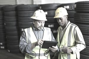 Men in the warehouse using a digital tablet.