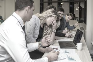 An employee sitting in a meeting showing a negative reaction and upsetting other employees at the meeting.