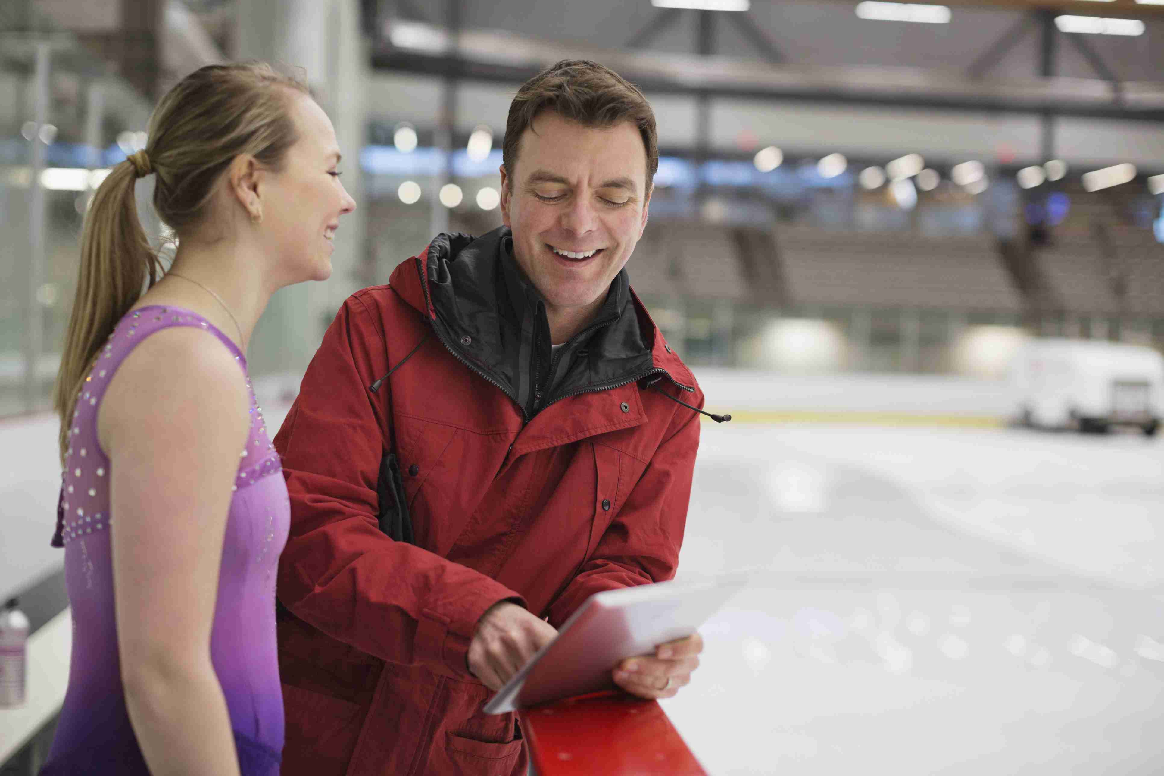 Female figure skater with coach discussing routine in skating rink