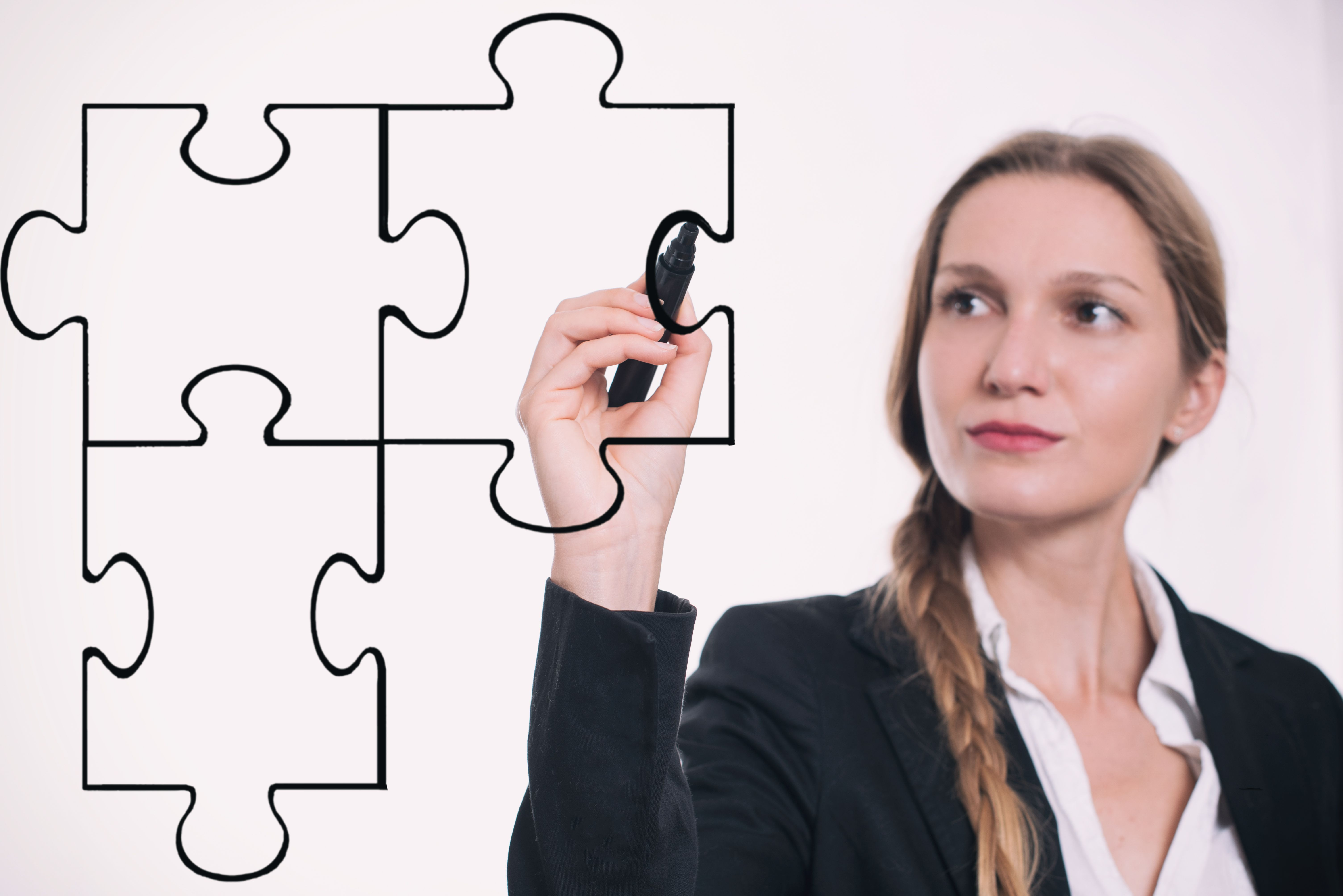 Woman drawing puzzle pieces fitting together.