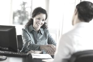 Woman preparing to ask management job interview questions while interviewing her candidate.