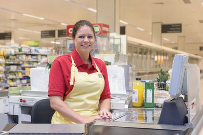 Portrait of smiling woman working at grocery checkout