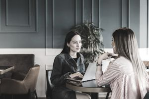 Shot of two businesswomen having a discussion while using a laptop