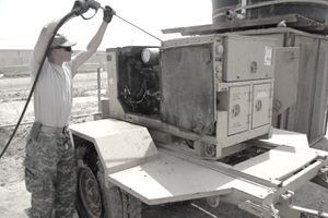 Spc. Bradley Berlau, a multichannel transmissions systems operator and maintainer cleans a generator prior to inspection for turn in on July 28 at Camp Liberty, Iraq.
