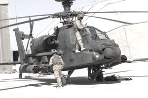 Two soldiers repairing an Apache AH-64 helicopter.
