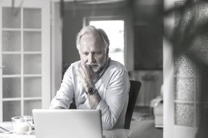Portrait of mature man using laptop at home