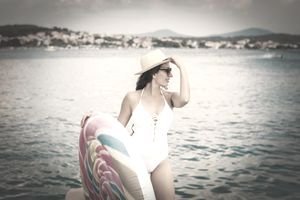Woman posing in a swimsuit with a pool float looking like a swimsuit model.