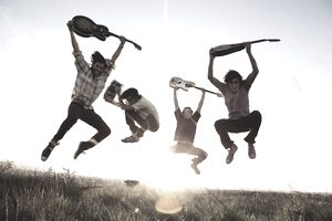 A band jumping into the air holding guitars and a drum during a photo shoot.