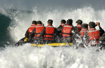 Basic Underwater Demolition/SEAL students encounter a large wave during a surf passage exercise.