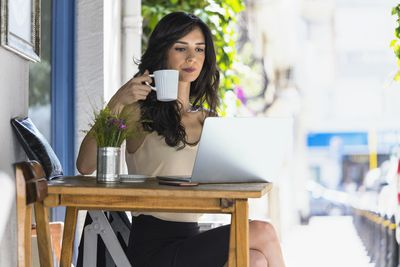Woman drinking coffee while looking online for a new job