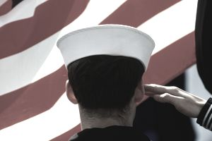 US Navy sailor saluting US flag