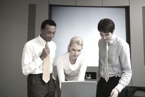 Businesswoman and two businessmen are using a laptop to write the requirements that their job analysis has identified.